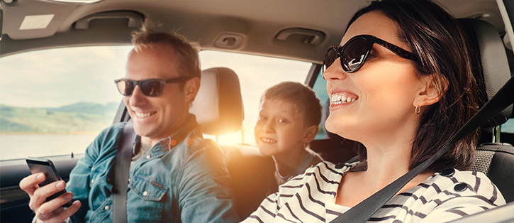 Smiling family in car with phone-1